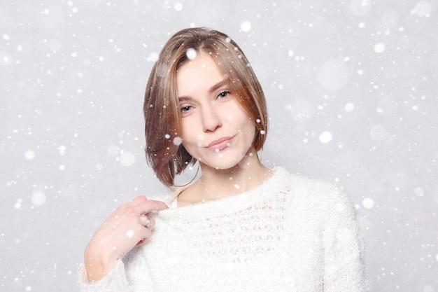 Снег, зима, рождество, здоровый образ жизни, счастье и концепция людей - молодая красивая милая девушка, показывающая разные эмоции. смех, улыбка, гнев, подозрение, удивление. на фоне снега