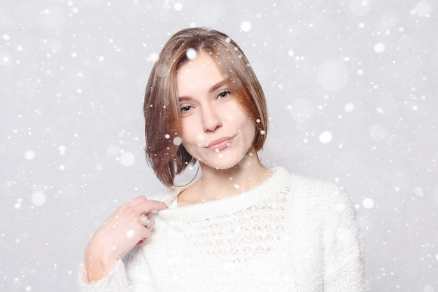 Snow, winter, christmas, healthy lifestyle, happiness and people concept - young beautiful cute girl showing different emotions. laughing, smiling, anger, suspicion, surprise. over snow background