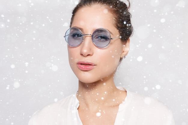 눈, 겨울, 크리스마스, 사람, 아름다움 개념-안경, 빈 벽, 스튜디오 초상화를 입고 흰색 공백 t- 셔츠에 아주 어린 소녀. 눈 배경 위에 안경에 웃는 갈색 머리 여자