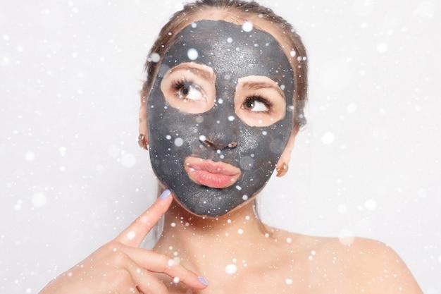 Снег, зима, рождество, люди, красота концепция маска для лица женщина. портрет красивой девушки, снимающей косметическую черную пилинг-маску с кожи лица на фоне снега