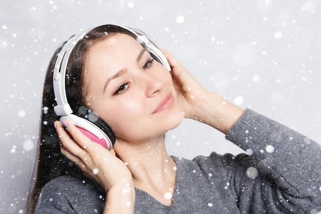 雪、冬、クリスマス、人、レジャー、テクノロジーのコンセプト-スマートフォンから音楽を聴き、雪の背景の上で踊るヘッドフォンで幸せな女性または10代の少女