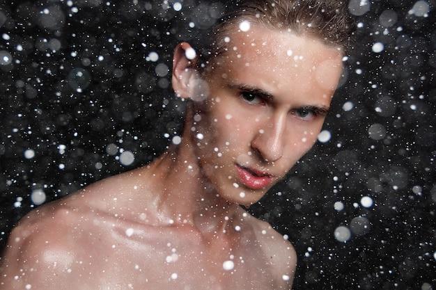 눈, 겨울, 크리스마스, 사람, 스킨케어 및 미용 개념 - 검은 눈 배경에 검은 머리를 한 젖은 젊은 남자. 면도한 가슴을 가진 초상화 남성. 남성 스킨 케어. 찢어진 근육질의 잘 생긴 남자