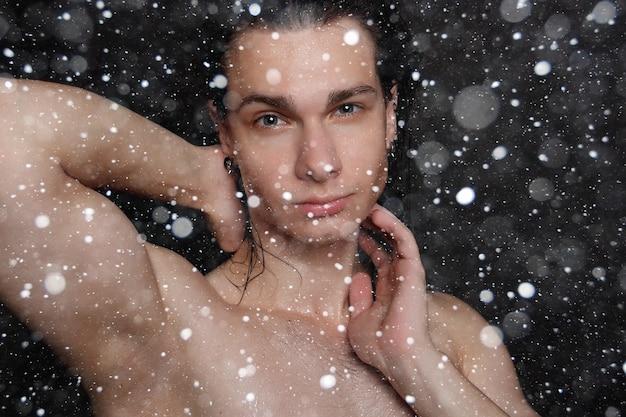 눈, 겨울, 크리스마스, 사람, 피부 관리 및 미용 개념 - 검은 눈 배경에 긴 검은 머리를 가진 젖은 젊은 남자. 면도한 가슴을 가진 초상화 남성. 남성 스킨 케어.