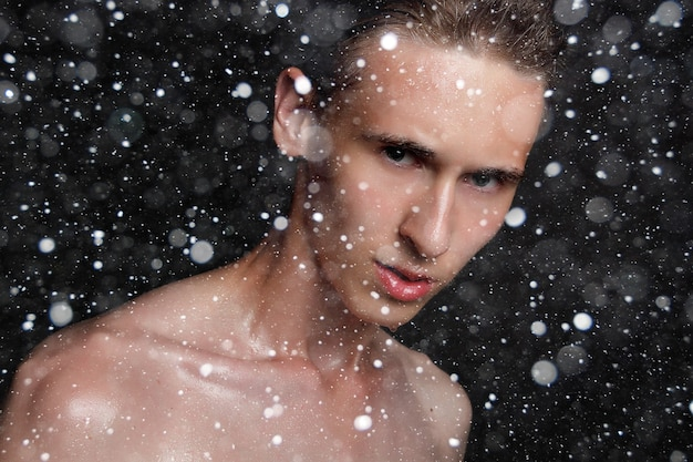 Snow, winter, christmas, people, skincare and beauty concept - wet young man with black hair on a black snow background. portrait male with shaved chest . men's skin care. ripped muscular handsome man