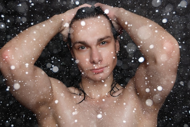 Snow, winter, christmas, people, skincare and beauty concept - wet young man with long black hair on a black snow background. portrait male with shaved chest . men's skin care.