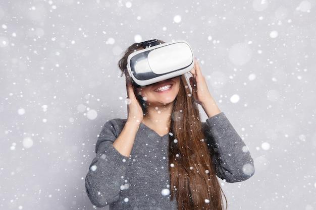 눈, 겨울, 크리스마스, 기술, 가상 현실, 엔터테인먼트 및 사람들 개념-행복한 여자 가상 현실 헤드셋 또는 3d 안경. 가상 현실을 가진 여자 눈 배경 위에 고글