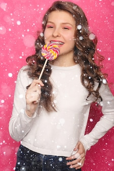 Snow, winter, christmas, teeth, emotions, health, people, dentist and lifestyle concept - woman with dental braces holding lollipop. healthy smile woman with clear brackets over snow background