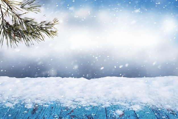 Snow on a wooden table on an abstract winter background with a spruce branch