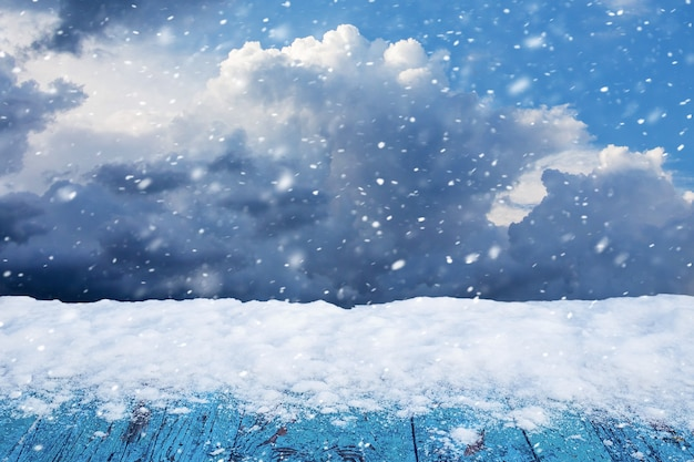 Snow on a wooden table on a background of winter cloudy sky during a snowfall