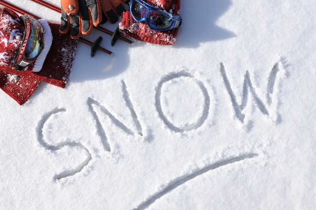 La neve di parola con i vestiti e le attrezzature da sci