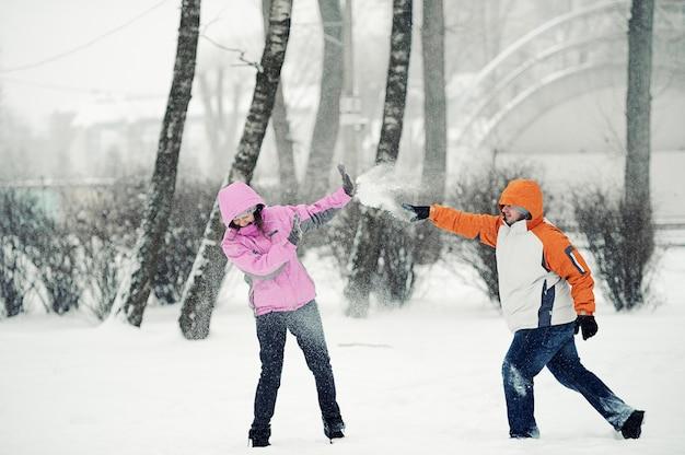 Битва снежками. пара весело играет в снегу на открытом воздухе