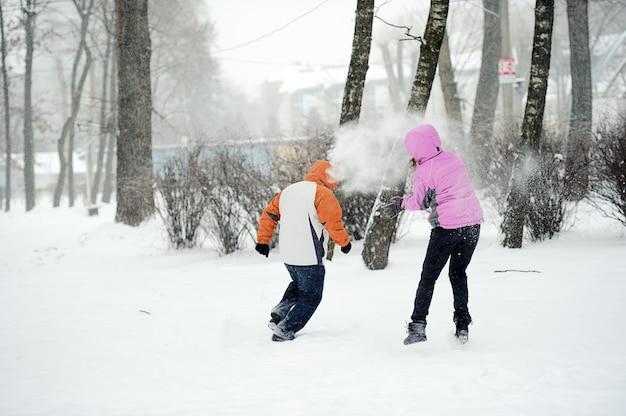 Битва снежками. зимняя пара весело играет в снегу на открытом воздухе