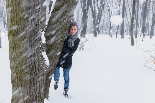 Snowball in front of smiling woman standing behind the tree