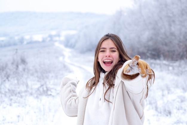 Snowball game in happy winter. playing with snow and having fun in winter park. activity smiling girl in winter travel.