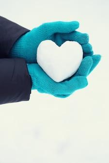 Снежок в форме сердца в руках