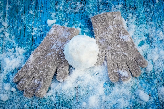 Snowball and mittens on a snowy wooden surface