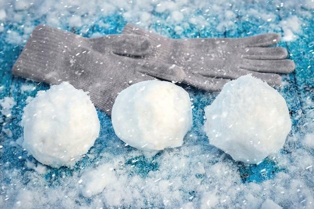 Снежки и варежки на заснеженной деревянной поверхности во время снегопада