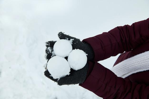 白い雪の背景に灰色の手袋をはめて手の雪玉。雪玉に焦点を当てます。