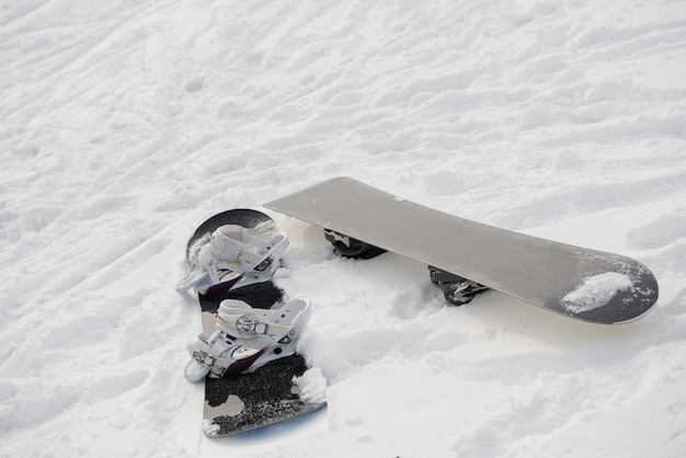 Snowboard on snowy slope in ski resort