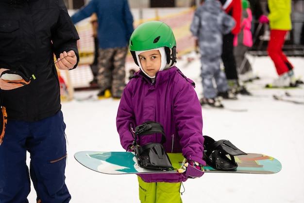 スノーボードウィンタースポーツ。暖かい冬の服を着て、スノーボードを学ぶ少女。冬の背景。