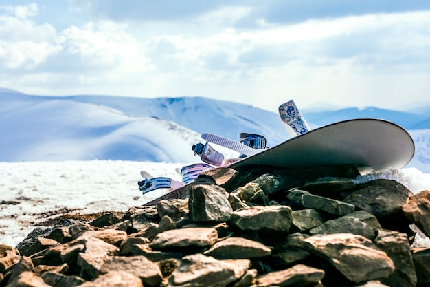 Snowboard with bindings on rocks over the snowy mountain landscape