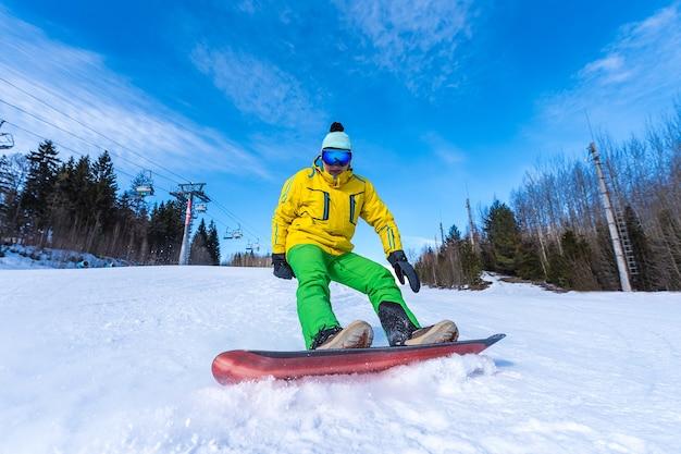 明るい晴れた日にスノーボーダーが雪にブレーキをかける