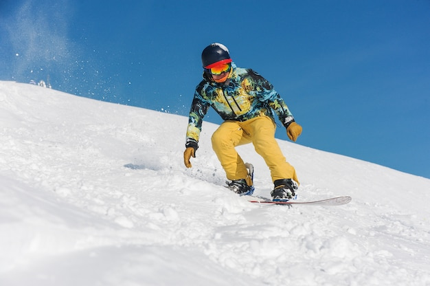 Snowboarder in bright sportswear riding down a mountain slope
