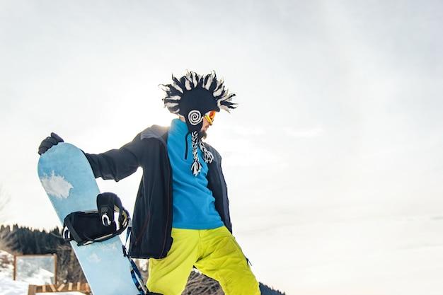 산에서 재미있는 모자를 쓴 스노보더 프리라이더가 내려갈 준비를 하고 있다