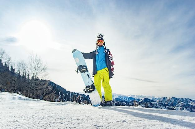 산에서 스노보더 프리라이더가 눈 덮인 산을 배경으로 내려갈 준비를 하고 있다