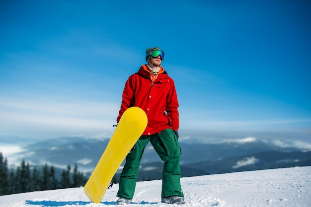 Snowboarder in glasses poses with board in hands, blue sky and snowy mountains. winter active sport, extreme lifestyle, snowboarding