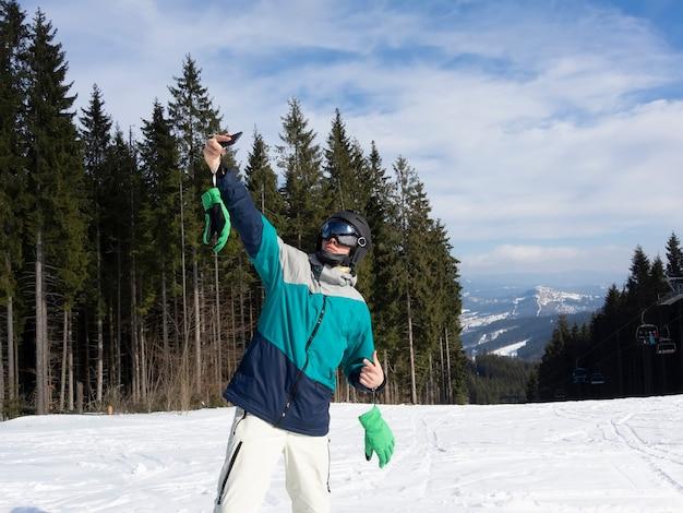 Сноубордист делает селфи на склоне горы