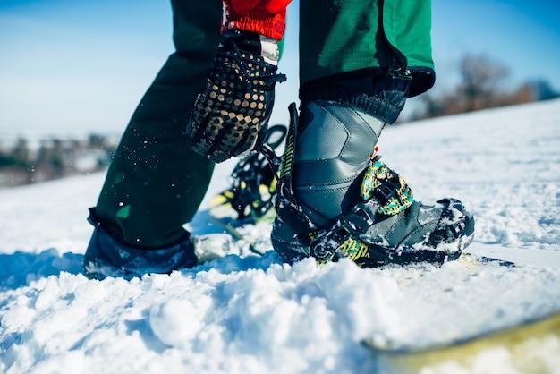 スノーボーダーの手はスノーボードファスニングクローズアップを固定します。ウィンターアクティブスポーツ、エクストリームライフスタイル、スノーボード