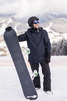 Сноубордист держать сноуборд на вершине холма крупным планом портрет, снежные горы, сноубординг на склонах.