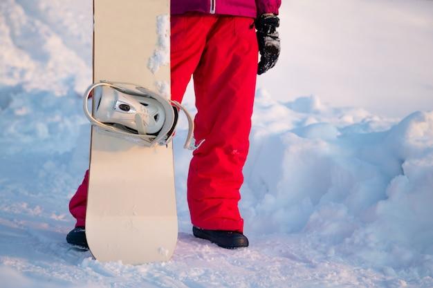 山の頂上にスノーボードを持って遠くを振り返るスノーボーダー