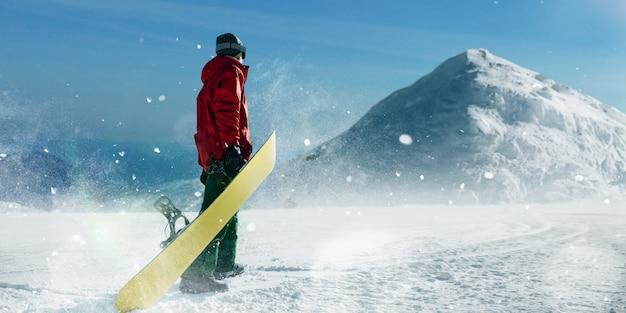 Сноубордист держит доску в руках, голубое небо и заснеженные горы. зимний активный спорт, экстремальный образ жизни, сноуборд