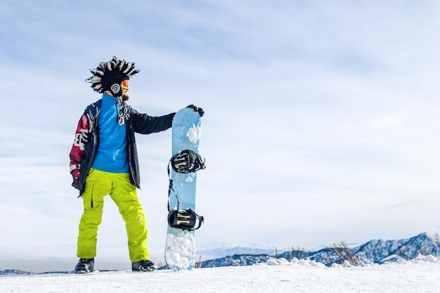 Сноубордист в лыжной маске с меховой большой шапкой-ирокез на фоне неба и зимних заснеженных гор