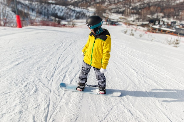 검은색 헬멧을 쓴 스노보더, 노란색 재킷은 스키 슬로프의 파란색 스노보드 위에서 미끄러집니다.