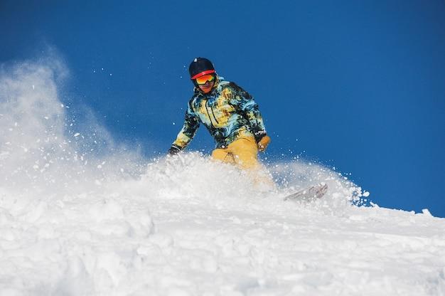 パウダーマウンテンスロープに乗って明るいスポーツウェアのスノーボーダー