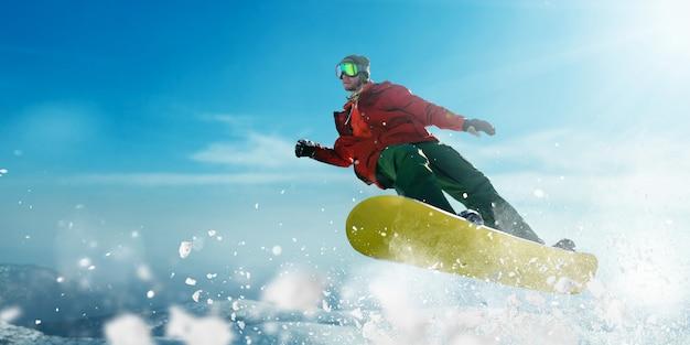 眼鏡をかけたスノーボーダーがジャンプし、スポーツマンが行動する。冬のアクティブスポーツ、極端なライフスタイル。山でのスノーボード