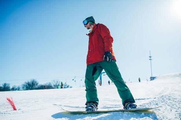 メガネのスノーボーダーが手でボードでポーズします。