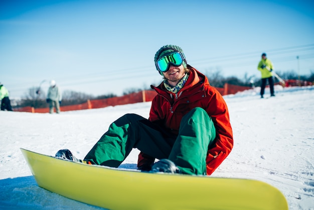 雪に覆われた斜面に座っているメガネのスノーボーダー。冬のエクストリームスポーツ、アクティブなライフスタイル。山でのスノーボード