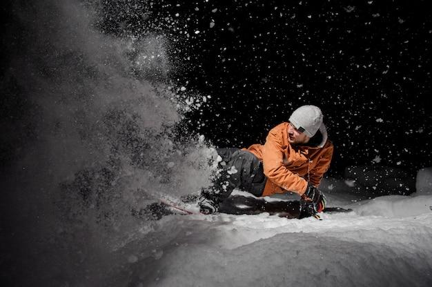 Сноубордист в оранжевой куртке верхом на снежной горке ночью