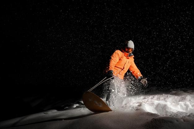 Сноубордист в оранжевой спортивной одежде и маске верхом на снежной горке ночью