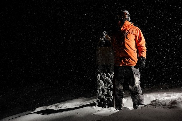 Сноубордист в оранжевой спортивной одежде и маске стоит с доской на снежной горке ночью