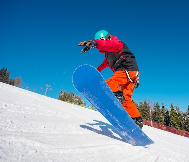 Snowboarder jumping in the air while riding on the slope at winter ski resort in the mountains