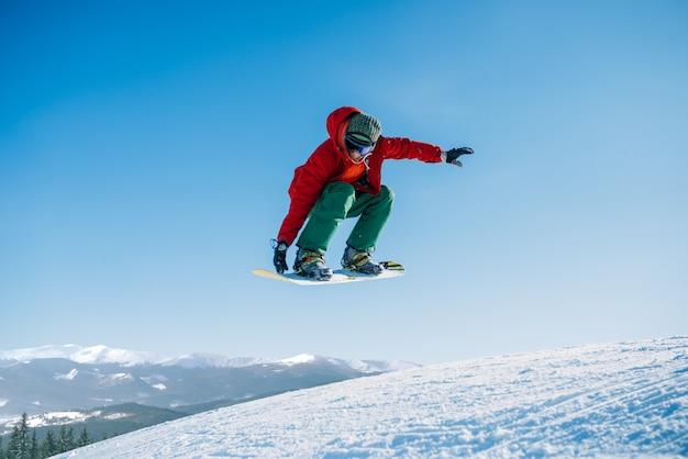 スノーボーダーは、スポーツマンのアクションでスピードスロープにジャンプします。冬のアクティブなスポーツ、極端なライフスタイル。山、青い空でスノーボード