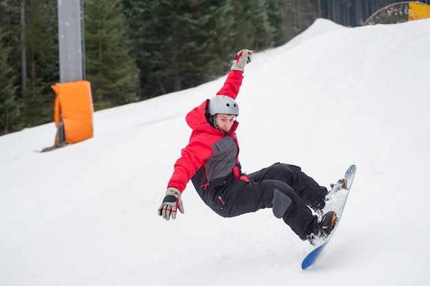 Snowboarder in the moment of falling on the snowy slope