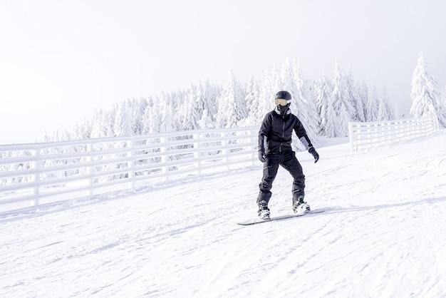 Snowboarder in movimento a cavallo giù per la collina nella località di montagna