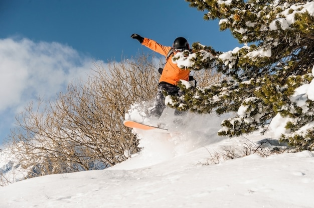 Snowboarder in orange sportswear jumping on the powder mountain slope