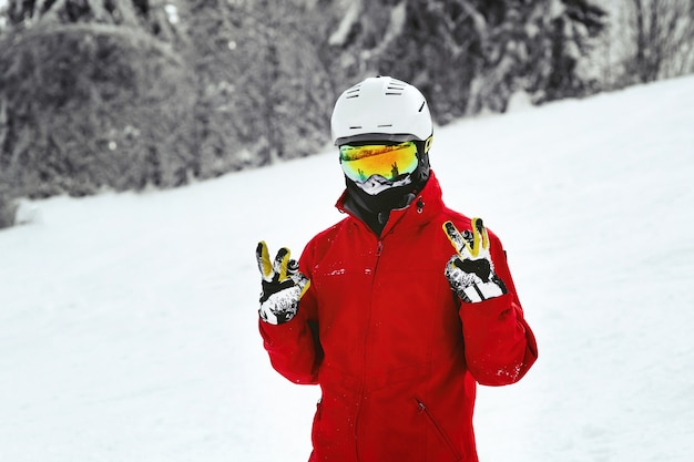 Snowboarder in red jacket, white helmet and yellow glasses poses on the hill